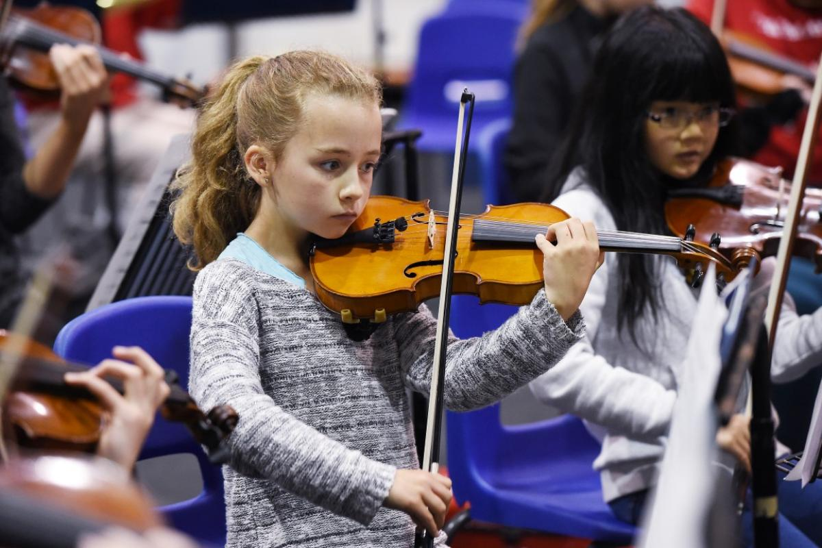 A young violinist from NYOS Junior Orchestra rehearsing at Strathallan School in July 2015