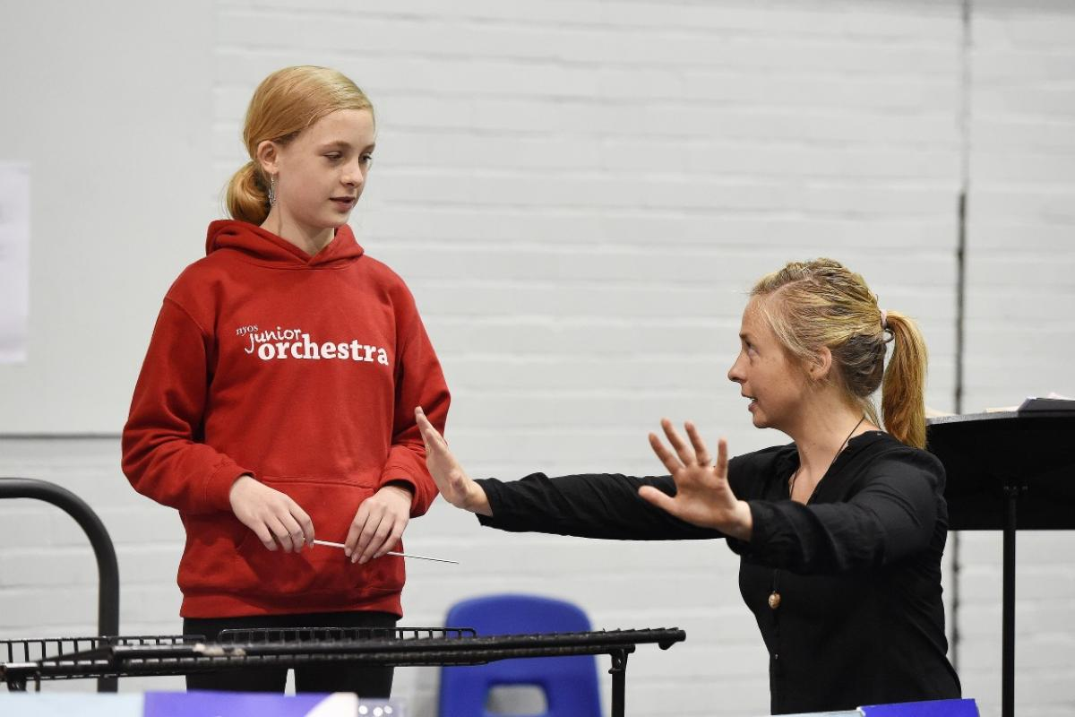 A member of NYOS Junior Orchestra receives a quick lesson from conductor Holly Mathieson