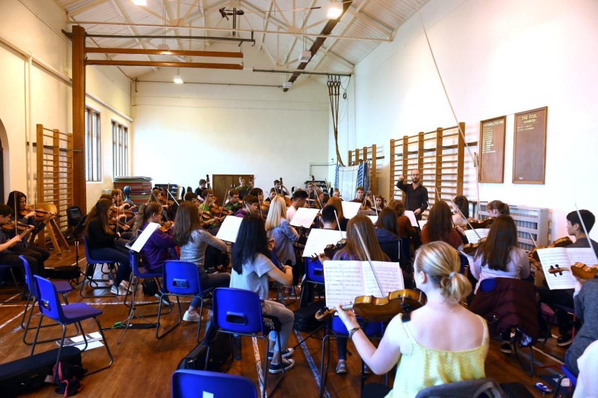 Tutor Chris George with NYOS Senior Orchestra String Section